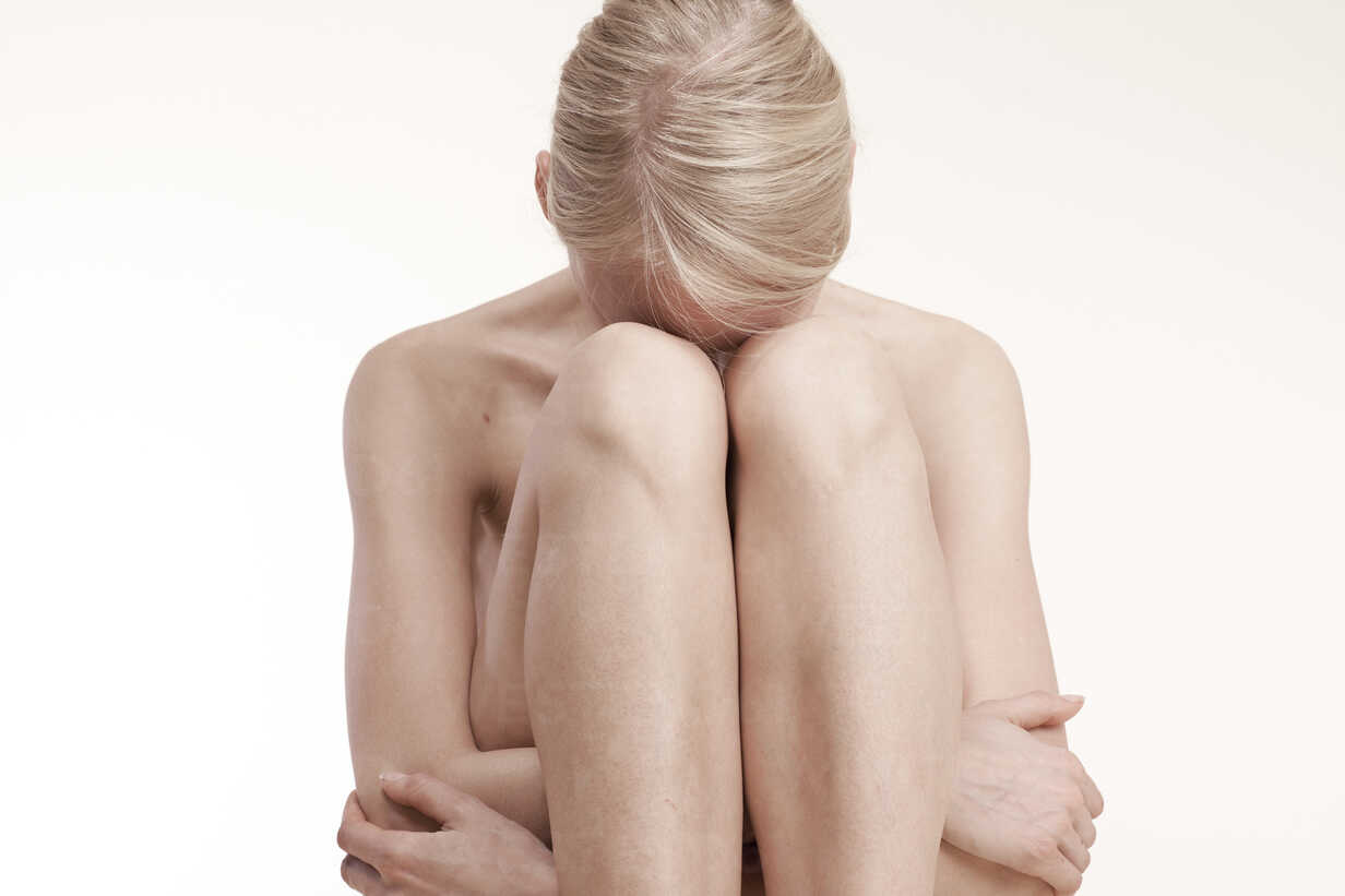 Despaired nude young woman sitting huddled on floor - DRF001485 - Stefan Rupp/Westend61
