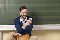 Smiling teacher in classroom looking at cell phone - MFRF000065