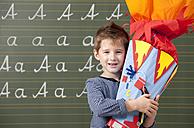 Happy boy with school cone at blackboard - MFRF000071