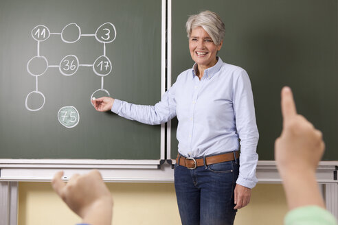 Smiling teacher at blackboard with arithmetic problem - MFRF000148