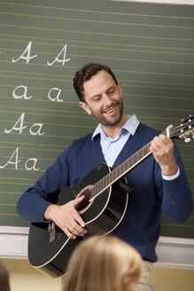 Teacher playing guitar in classroom - MFRF000086