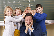 Teacher with playful pupils in classroom - MFRF000115