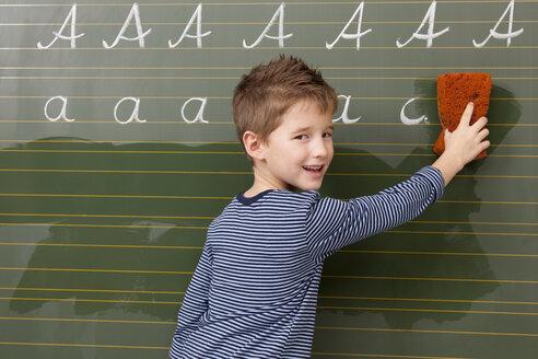 Schoolboy at blackboard wiping away letter A - MFRF000093