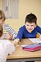Pupils handing over slip of paper in classroom - MFRF000105