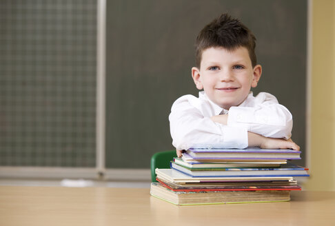 Portrait of smiling schoolboy in classroom - MFRF000108