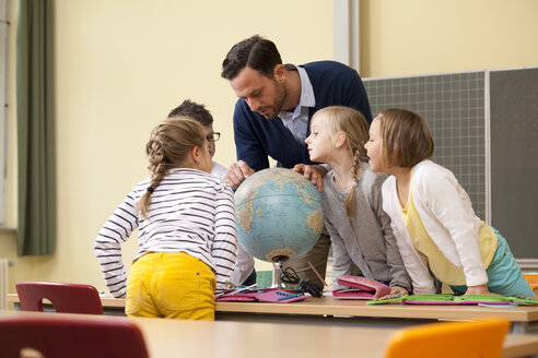 Teacher and pupils looking at globe in classroom - MFRF000129