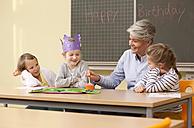 Teacher and schoolgirls celebrating birthday in classroom - MFRF000140