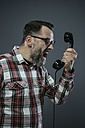 Man screaming into retro telephone in front of grey background - IPF000208