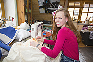 Portrait of smiling female teenager using sewing machine in a workshop - SARF001614