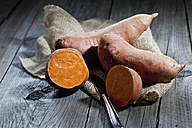 Row sweet potatoand knife on jute, wood - CSF024726