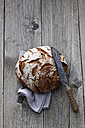 Round crusty bread, old bread knife and kitchen towel on wood - CSF024731