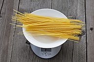 Row spaghetti on plate and scale on wood - CSF024742