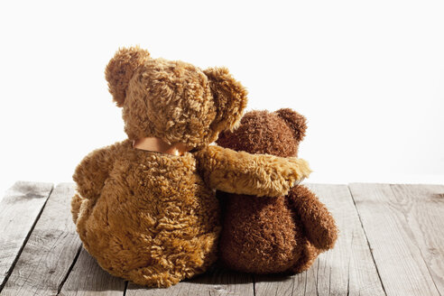 Two teddy bears, arm on shoulder, back view on wood - CSF024763