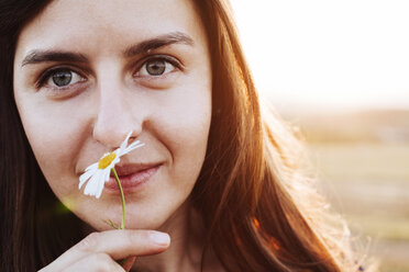 Portrait of smiling woman smelling flower - BZF000069