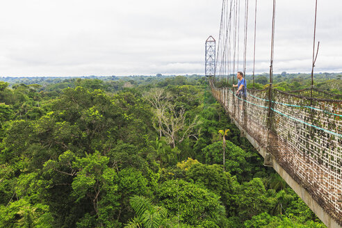 Ecuador, Amazon River region, tourist on suspension bridge above rain forest - FOF007769