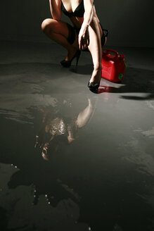 Young woman wearing lingerie mirroring in spilled fuel - VEF000038