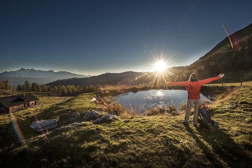 Austria, Altenmarkt-Zauchensee, young woman in the mountains at sunrise - HHF005185