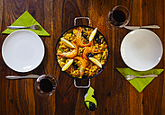 Laid wood table with fresh paella and red wine - KRPF001342