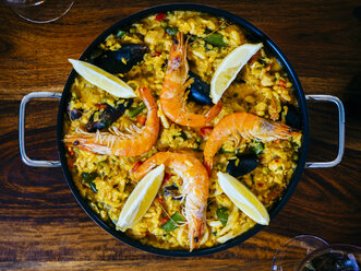 Fresh paella in pan on wooden table - KRPF001343