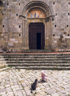 Italy, Tuscany, Montefollonico, girl and cat in front of a church - GSF001005