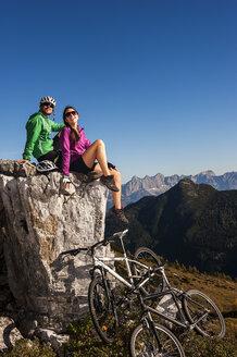 Austria, Altenmarkt-Zauchensee, young couple with mountain bikes in the mountains - HHF005195