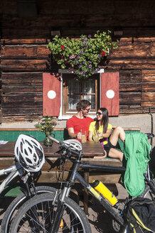 Austria, Altenmarkt-Zauchensee, young couple with mountain bikes at alpine hut - HHF005202