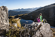 Austria, Altenmarkt-Zauchensee, young couple with mountain bikes in the mountains - HHF005208