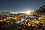 Austria, Altenmarkt-Zauchensee, young woman in the mountains at sunrise - HHF005135