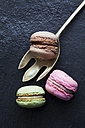 Three different macarons and a spoon on dark background - CSF024790