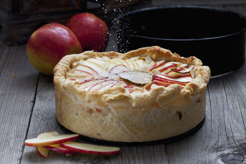 Sprinkling baked apple pie with icing sugar - CSF024774