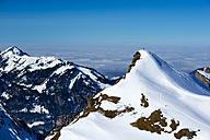 Germany, Bavaria, Allgaeu, Allgaeu Alps, couple standing on summit in winter - WGF000618