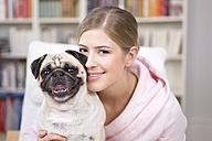 Portrait of young woman with pug - DRF001598