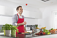 Smiling man juggling with tomatoes in kitchen - PDF000833