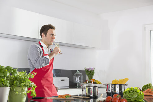 Man relaxing with glass of sparkling wine in kitchen - PDF000836