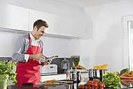 Smiling man looking at digital tablet in the kitchen - PDF000839