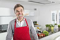 Portrait of man with cooking spoon between his teeth - PDF000842