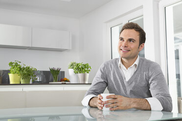 Smiling man sitting in kitchen with cup of coffee - PDF000848