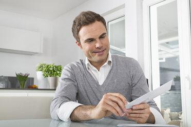 Smiling man sitting in kitchen opening envelope - PDF000851