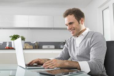 Smiling man sitting in kitchen using laptop - PDF000854