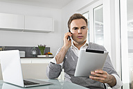 Man sitting in kitchen with laptop using digital tablet and smartphone - PDF000857