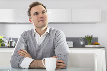Portrait of smiling man sitting in kitchen with cup of coffee - PDF000860