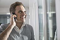 Portrait of smiling man telephoning with smartphone - PDF000866