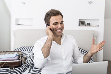 Smiling businessman sitting on bed telephoning with smartphone - PDF000894