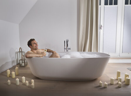 Man relaxing in bathtub with glass of champagne - PDF000877