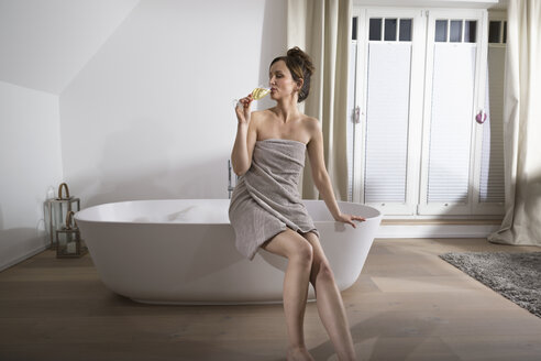 Woman sitting on the edge of modern bathtub drinking champagne - PDF000880