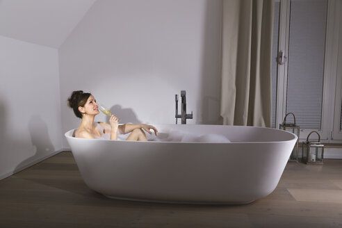 Smiling woman relaxing in modern bathtub with glass of champagne - PDF000886
