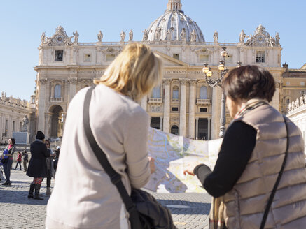 Italy, Rome, Tourists with map in front of St Peter's Basilica - LA001351