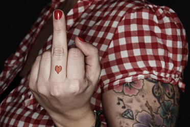 Woman with tatoos giving the finger - STK001206