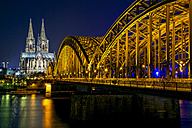 Germany, Cologne, illuminated Cologne Cathedral and Hohenzollern bridge at night - YRF000075