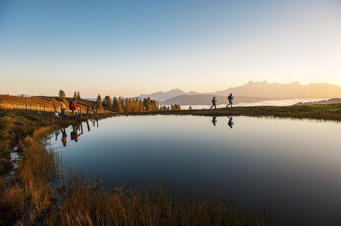 Austria, Altenmarkt-Zauchensee, hikers at mountain lake in the Lower Tauern - HHF005141